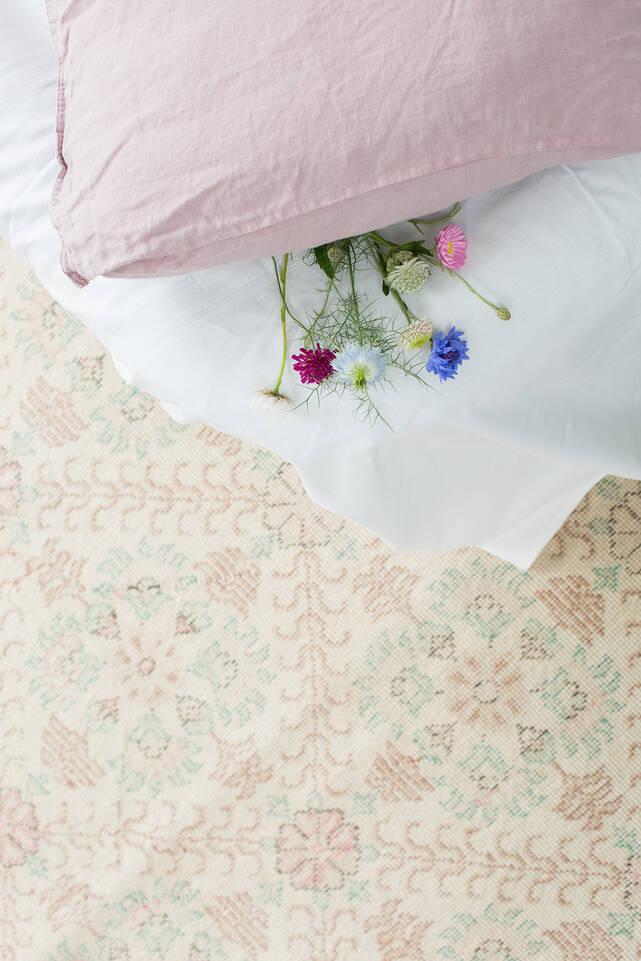 Hvidt  colored vintage - turkiet - tæppe  i en soveværelse.