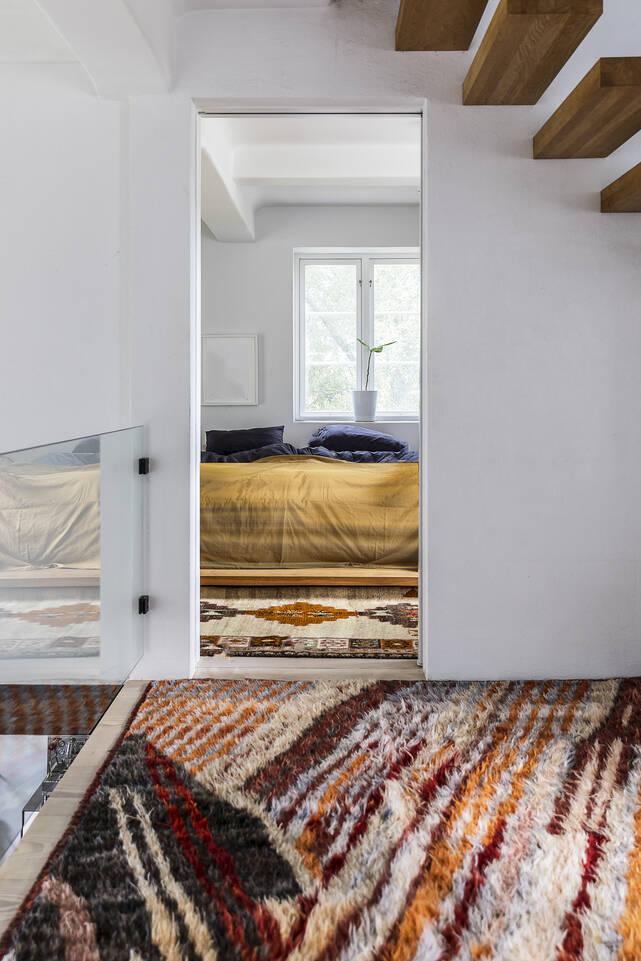 Brunt / gul aflangt moroccan berber - afghanistan - tæppe  i en soveværelse.